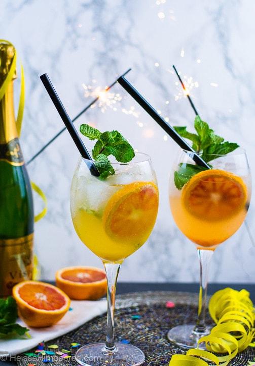 Ein Aperitif mit Gin und Prosecco zu Silvester. Es brennen Wunderkerzen