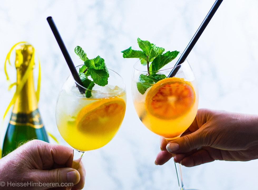 Zwei Gläser mit Gin und Prosecco stoßen an