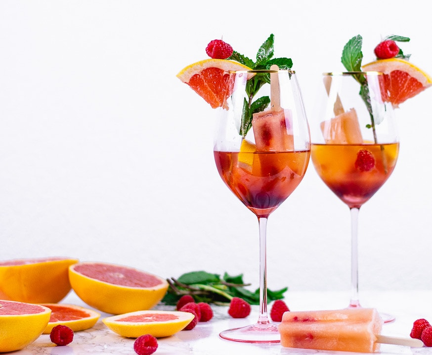 Zwei Gläser Himbeer Spritz. Daneben liegen Blutorangen, Eis und Himbeeren als Deko