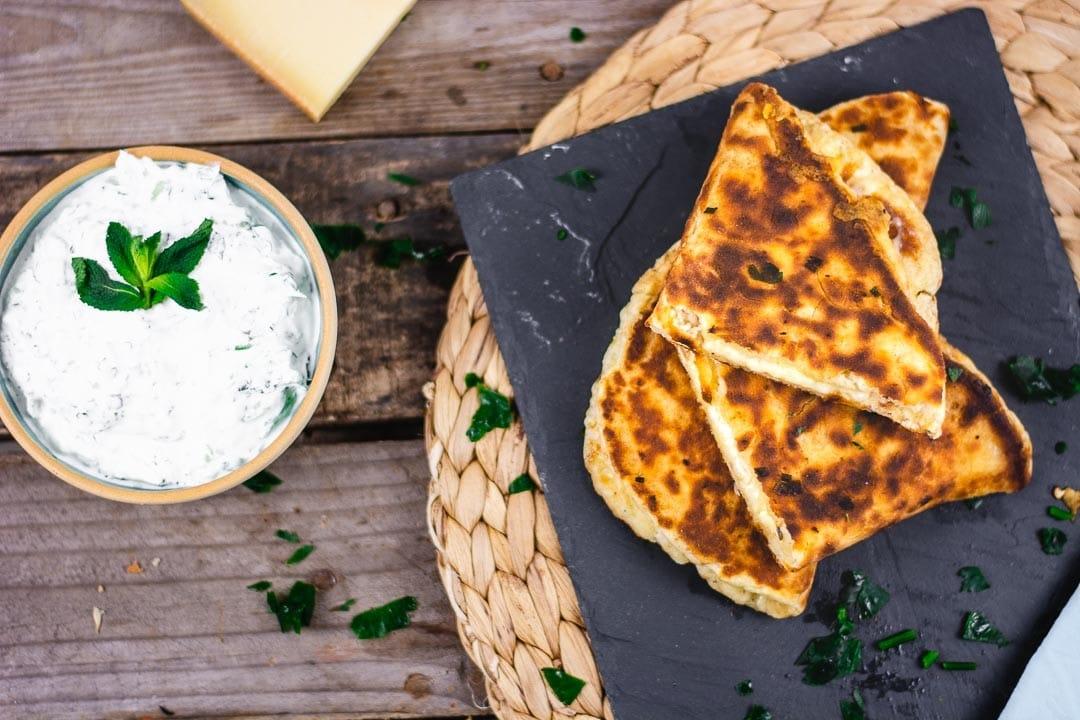 Mehrere Käse Naan gestapelt auf einer Platte. Daneben ist ein Dip