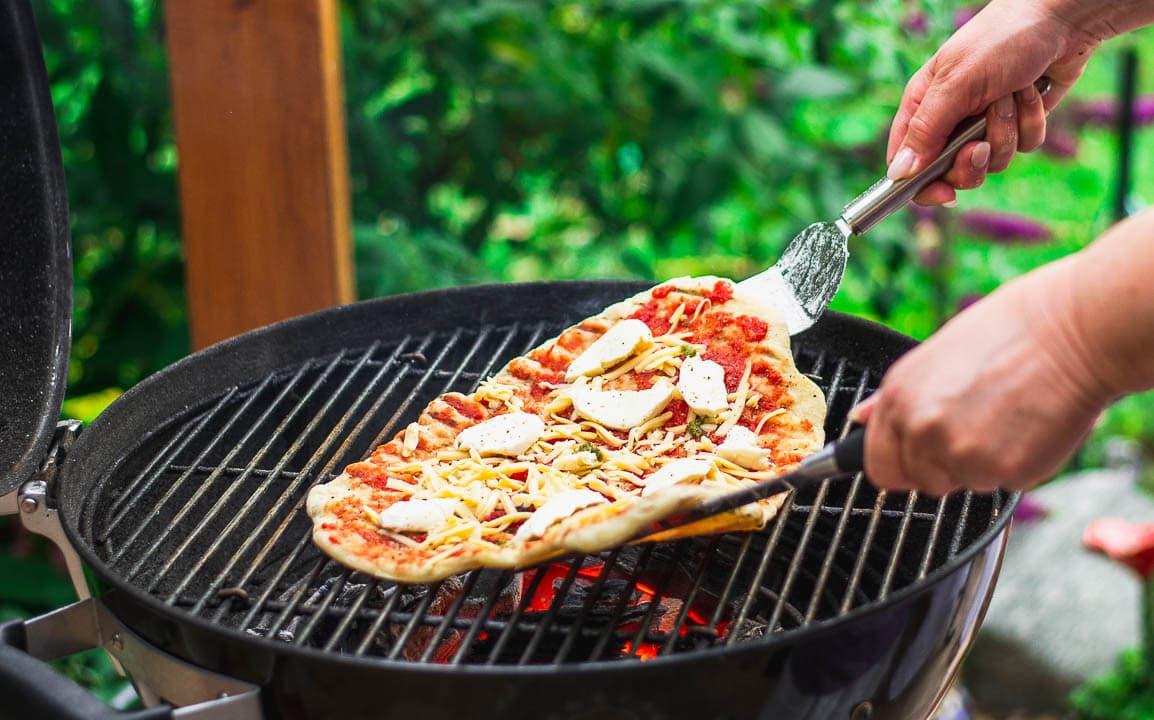 Die Pizza wird auf einen Grill gelegt