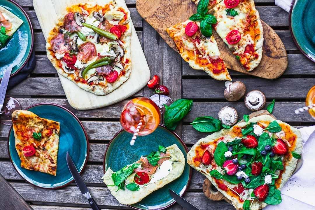 Ein Tisch voll mit gegrillter Pizza