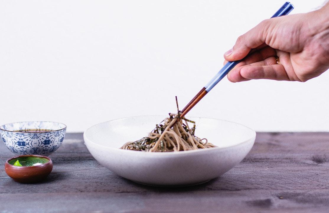Zwei Stäbchen nehmen Soba Nudeln aus einem Teller