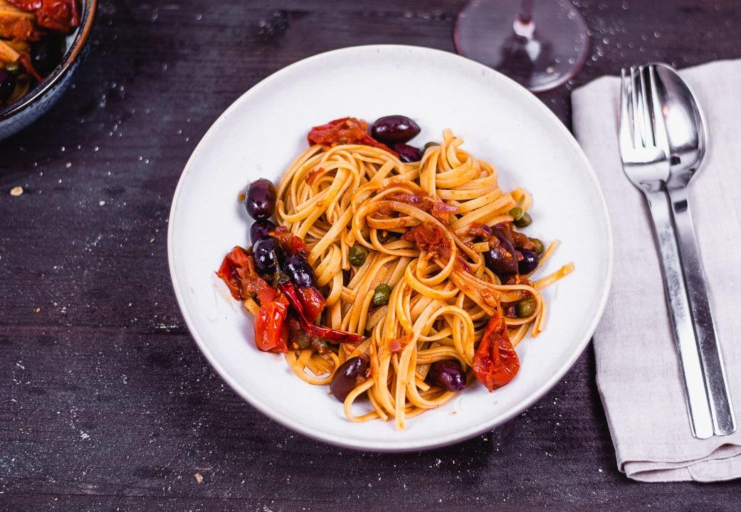 Spaghetti Puttanesca vegetarisch auf einem Teller mit Besteck daneben