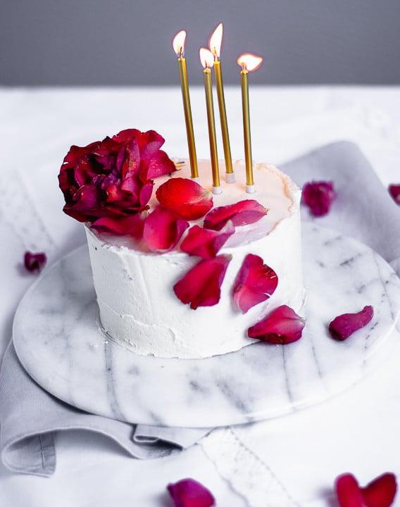 Vier Kerzen werden gerade ausgepustet, auf dem Geburtstagskuchen