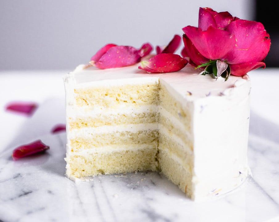 Ein angeschnittener Geburtstagskuchen. Die Creme innen ist weiß und die Böden haben die Farbe von Vanille. Oben drauf liegt eine Rose und Rosenblätter