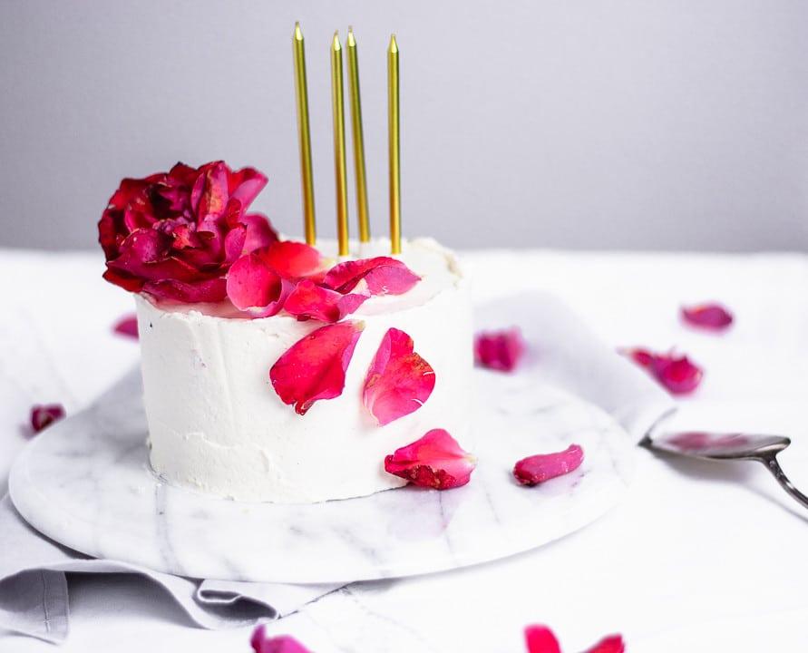 Vier goldene Kerzen auf einem weißen Geburtstagskuchen