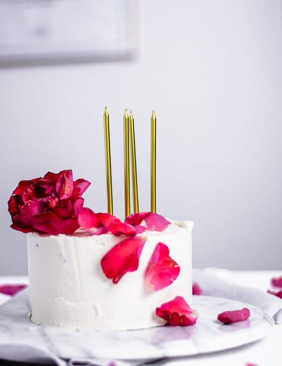 Der Geburtstagskuchen mit vier Kerzen von der Seite. Der Kuchen ist in eine weiße Cremeschicht gehüllt