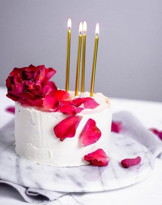 Ein Geburtstagskuchen mit Rosenblätter und goldenen, brennenden Kerzen