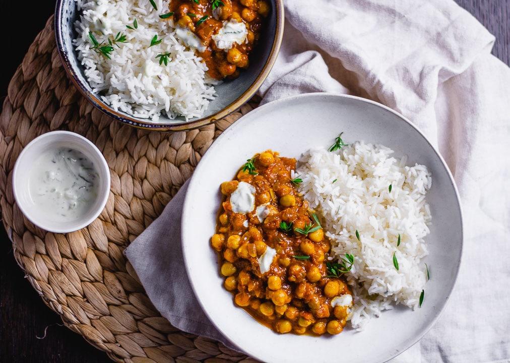 Zwei Teller mit Kichererbsen Curry auf einem Tisch