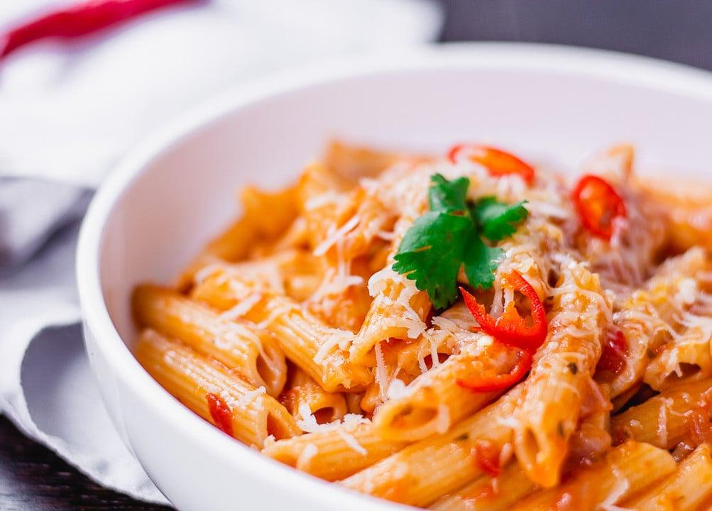 Ein Teller mit Pasta Arrabiata, Parmesan und Chili