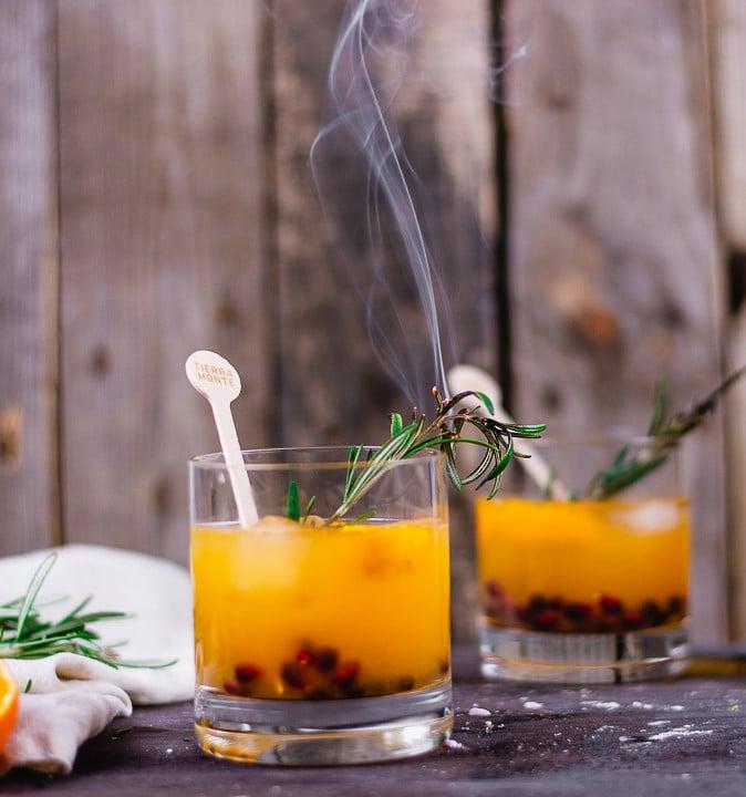 Zwei Rum Cocktails Gläser, die mit eine orangen Flüssigkeit und Cranberries gefüllt sind