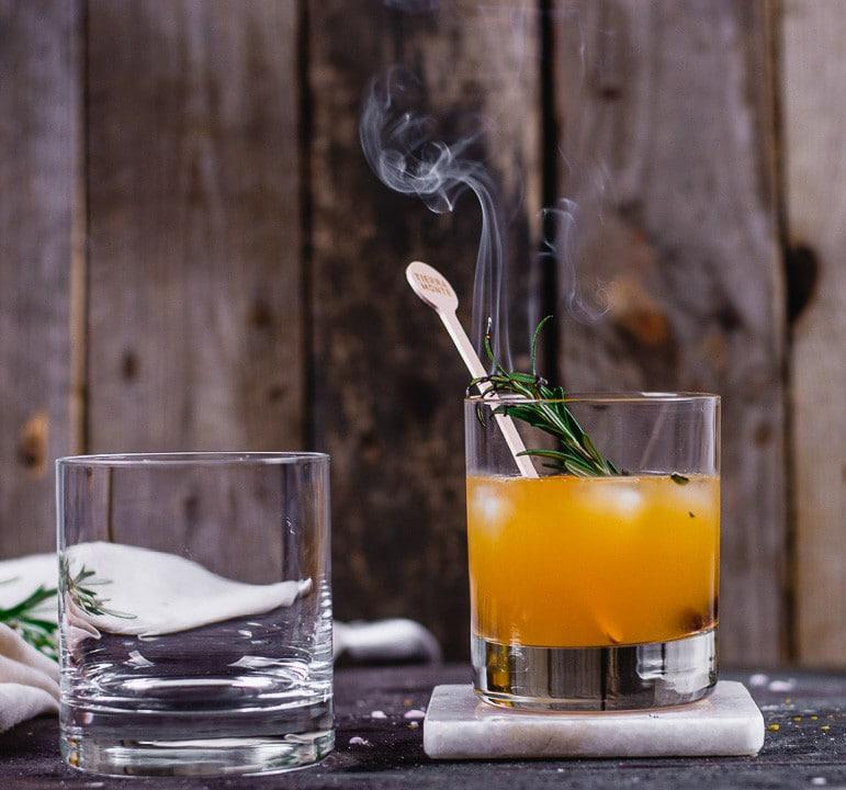 Der Rosmarinzweig raucht im Rum Cocktail