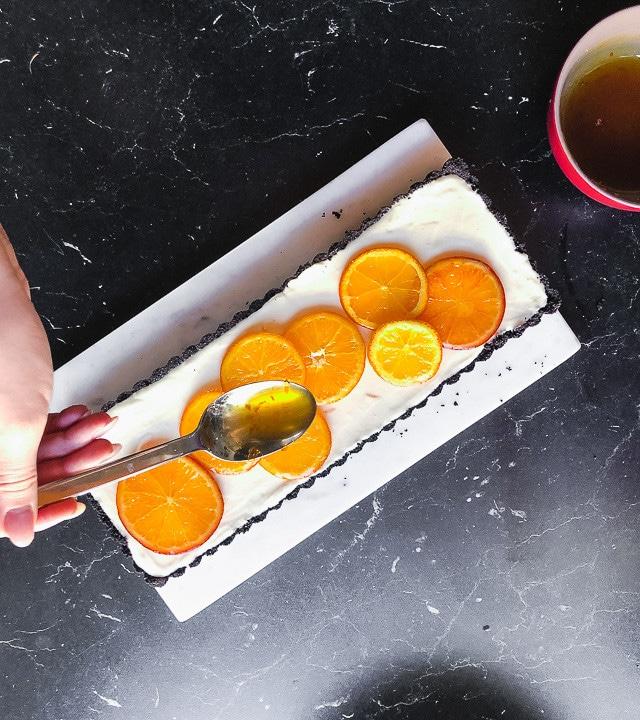 Orangensirup wird auf Tarte geträufelt
