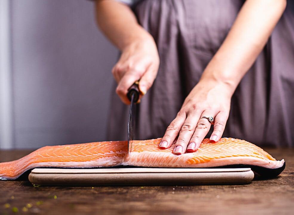 Ein Lachs wird halbiert mit einem Messer