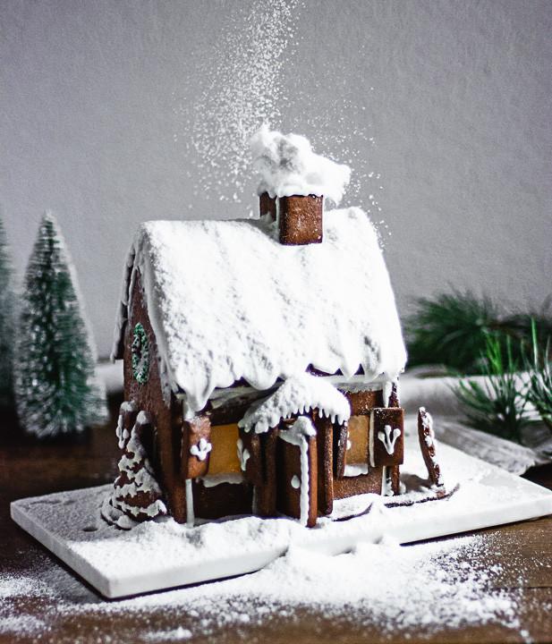 Ein Lebkuchenhaus wird eingeschneit