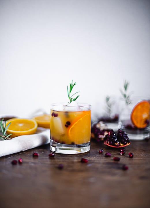 Ein Weihnachtsaperitif im Glas mit Eiswürfel, Orangen, Cranberries und Deko