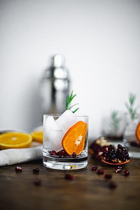 Im Hintergrund ist ein Cocktailshaker. Davor steht eine Weihnachtsaperitifglas ohne Inhalt