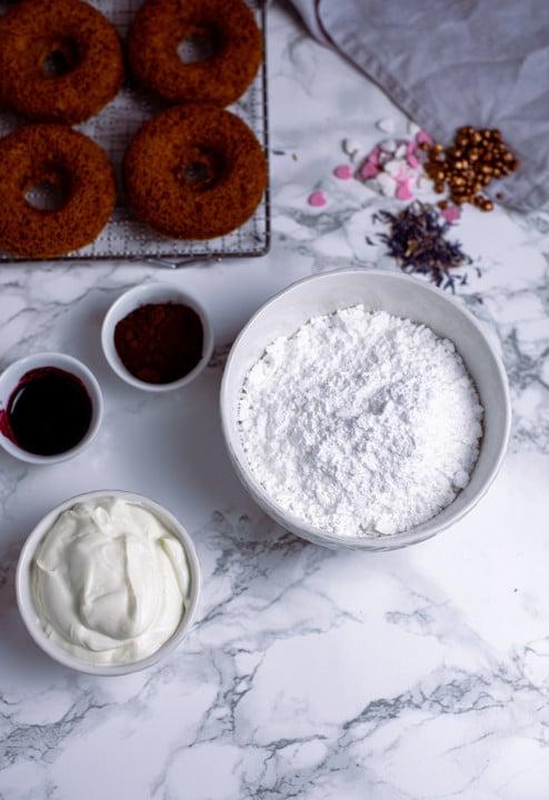 Für die Glasur benötigen wir Puderzucker, Joghurt, Kakaopulver und Beerenmarmelade.