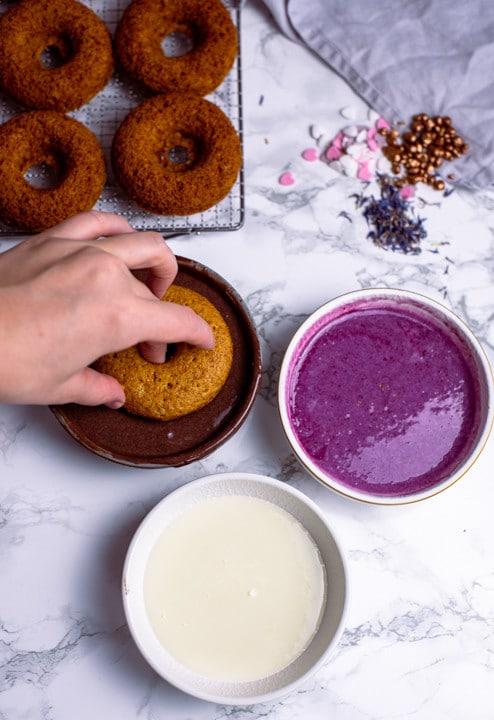 Ein Donut aus dem Backofen wird in die mit Kakao verfeinerte Glasur getaucht.