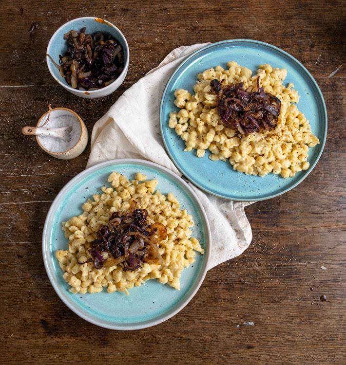 Zwei Portionen Käsespätzle stehen auf einem beigen Tischtuch auf einem alten Tisch aus dunklem Holz. Die Teller sind jeweils Türkis. Links oben im Bild steht eine Schale mit Salz und eine Schälchen mit Röstzwiebeln.