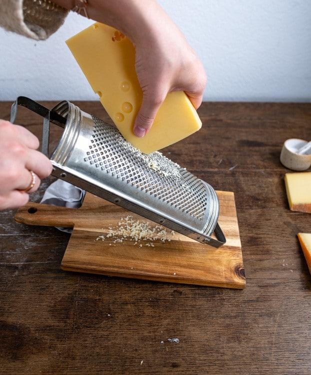 Der Käse wird mit Hilfe der Reibe fein gerieben.