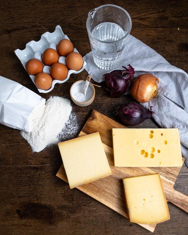 Die Zutaten, die für die Käsespätzle benötigt werden liegen auf dem Tisch. Im Uhrzeigersinn sind das Eier, Salz, Mineralwasser, Zwiebeln, verschiedene Bergkäse und Mehl.