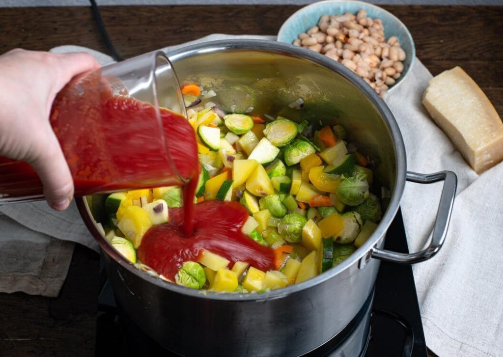 Außerdem kommen Dosentomaten mit in den Topf in dem sich bereits Gemüse und Weißwein befinden. Im Hintergrund zu sehen sind die weißen Bohnen und ein Stück Parmesan.