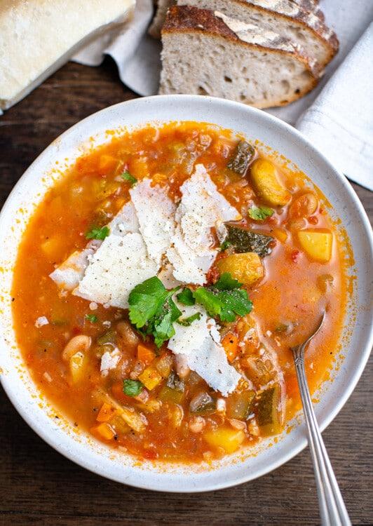 Eine volle Schüssel Minestrone ist zu sehen. Sie ist garniert mit Parmesanhobeln. Im Teller liegt ein Löffeln. Die verschiedenen Zutaten der Minestrone sind gut zu erkennen. Man sieht Rosenkohl, Kartoffeln, Bohnen, Zucchini und Karotte.