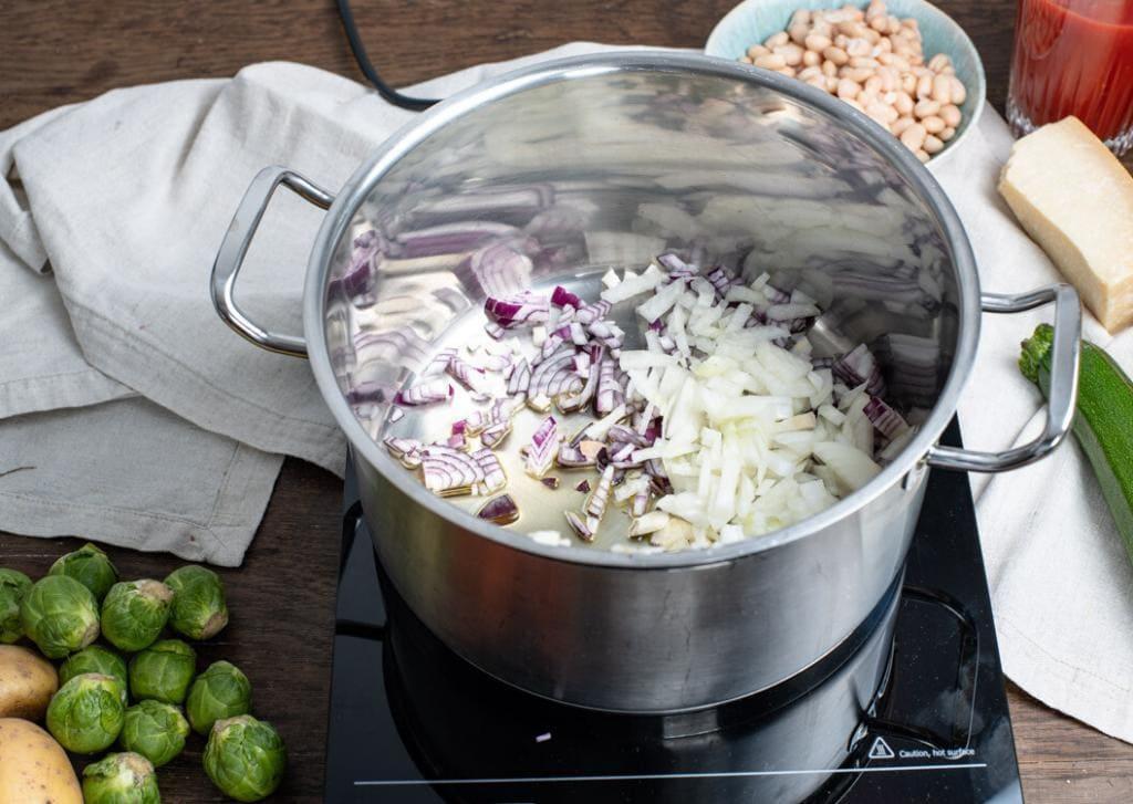 In einem großen Edelstahltopf befinden sich Zwiebeln und Knoblauch mit etwas Olivenöl. Die weiteren Zutaten der Minestrone liegen darum herum verteilt.