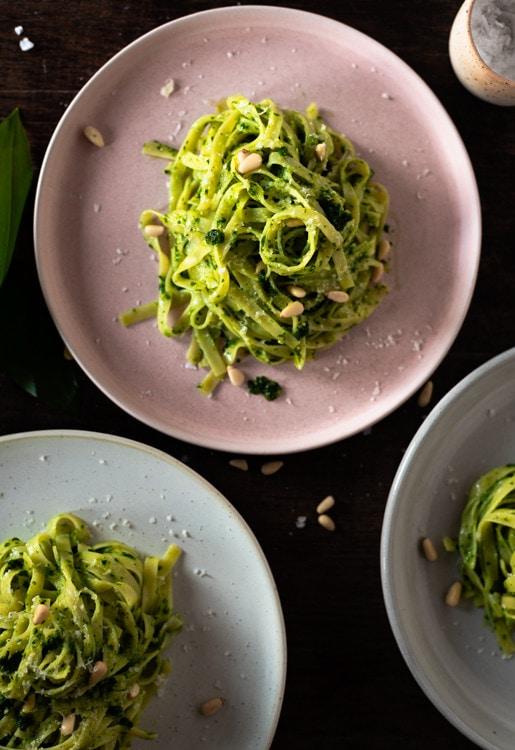 Drei Teller mit Bärlauchpesto. Der Teller im Fokus ist hellrosa, die grünen Pestonudeln heben sich deutlich davon ab.