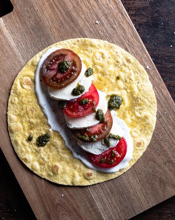 Ein Wrap gefüllt mit Tomate, Mozzarella und Pesto aber noch nicht aufgerollt