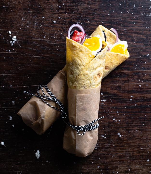 Zwei gefüllte Wraps mit Aubergine, Tomate, Ei und Zwiebel