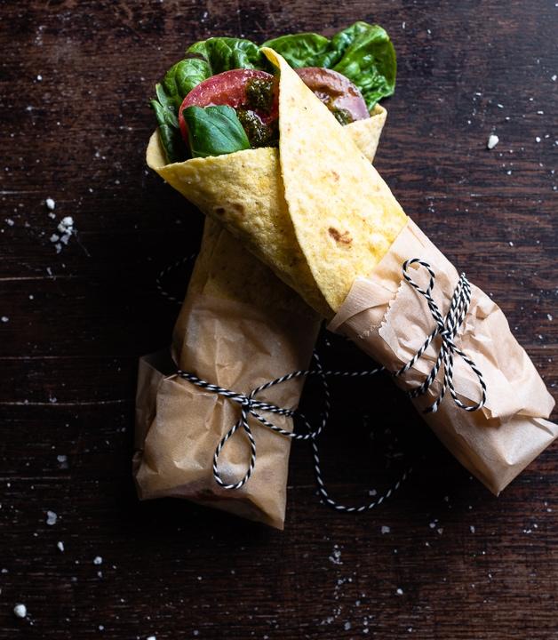 Zwei gefüllte Wraps mit Salat, Tomate und Basilikum