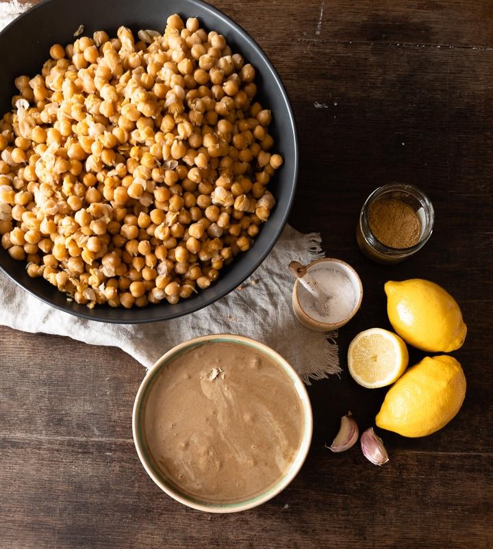 Die Zutaten für den Hummus sind weich gekochte Kichererbsen, Tahini, Kreuzkümmel, Zitronensaft, Salz und Knoblauch.