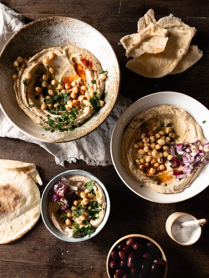 Cremiger Hummus, serviert mit Olivenöl, Pitabrot und frischen Zwiebeln.