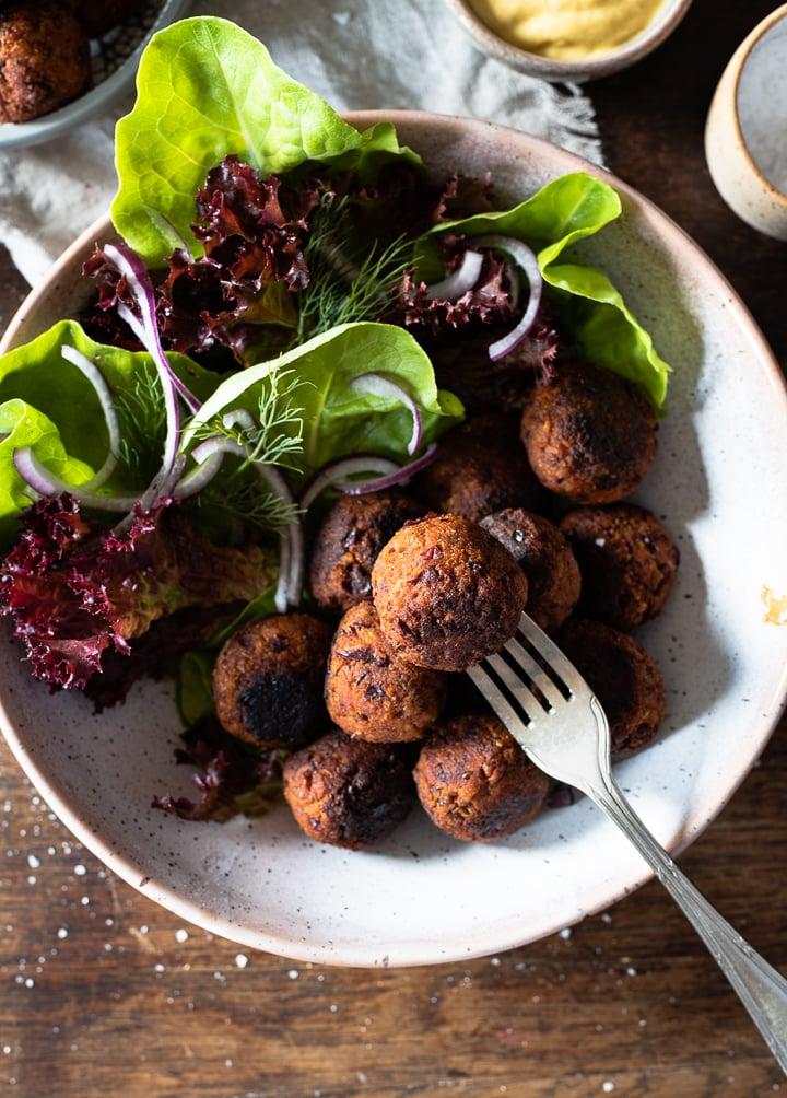 Vegetarische Hackbällchen auf einem Teller mit Salat und einer Gabel