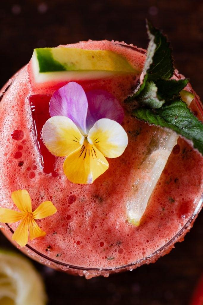 Serviert wird der Wassermelonen Cocktail auf Eis mit Minze, Limette und essbaren Blüten.
